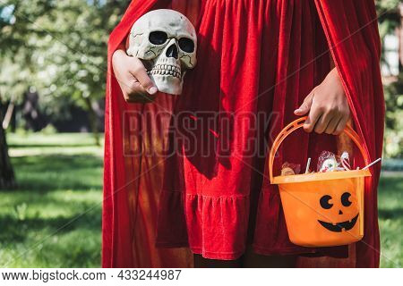 Partial View Of Girl Wearing Red Halloween Costume And Holding Skull And Bucket Of Candies