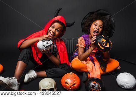 African American Siblings In Halloween Costumes Holding Carved Pumpkins On Black