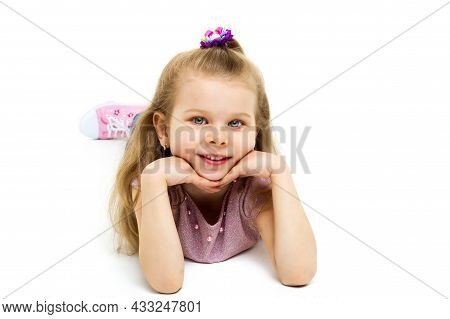 Charming Girl Lying On Floor With Hands Under Her Chin. Adorable Preschool Gray Eyed Girl Dressed Je
