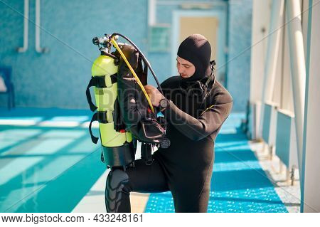 Male diver puts on oxygen tank, diving school