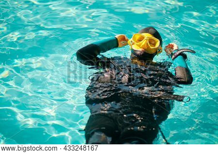 Female diver in scuba gear poses in pool, top view