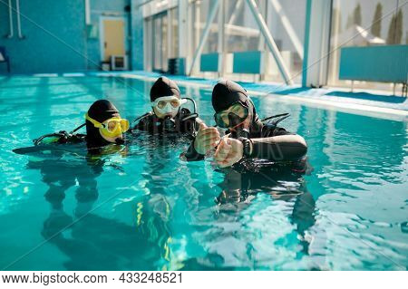 Instructor and divers in aqualungs, dive lesson