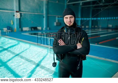 Male diver poses in scuba suit, diving school