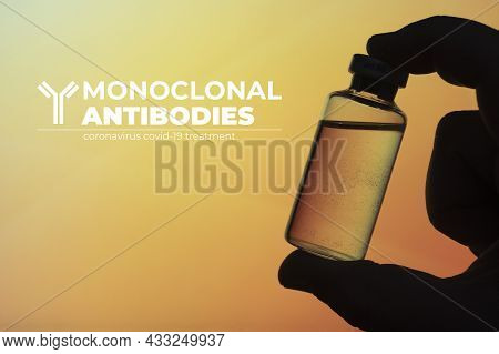 Monoclonal Antibodies Concept Image: Silhouette Of A Man Holding A Vial On Gradient Yellow And Orang
