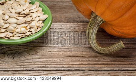 a bowl of fresh pumpkin seeds on weathered rustic wood background, fall harvest and holidays concept