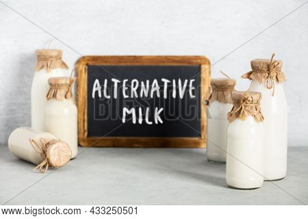 Non dairy plant based milk in bottles and chalkboard with Alternative milk lettering on light background. Alternative lactose free milk substitute