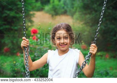 Child Playing On Outdoor Playground. Kids Play On School Or Kindergarten Yard. Active Kid On Colorfu