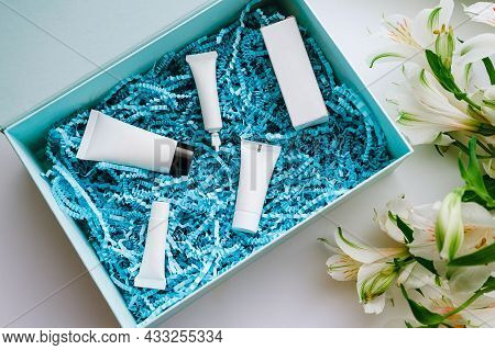 Beauty Box With Samples Of Cosmetics For Face Care With Blue Packaging Paper Shavings And White Alst