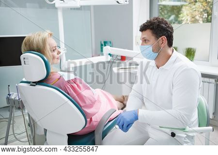 Male Dentist Wearing Medical Face Mask, Working With Female Patient