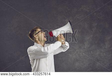 Serious Young Caucasian Male Activist Loudly Makes Loud Announcement Using Loudspeaker.