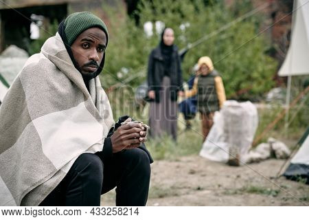 Puzzled young Black man wrapped into blanket sitting in migrant camp and drinking tea in cold weather