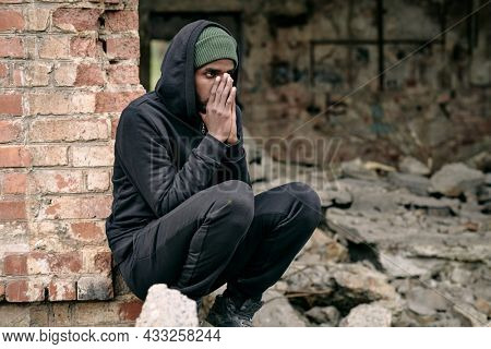 Distraught young Black refugee man in black outfit crouching at ruined building and covering face with hands