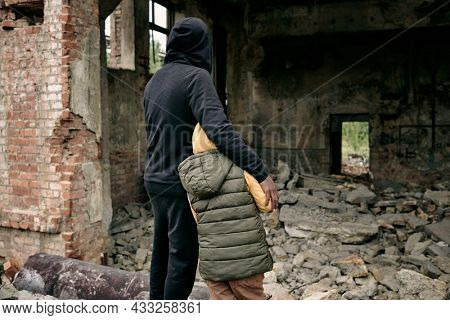 Rear view of father embracing child and looking at ruins of house after hostilities