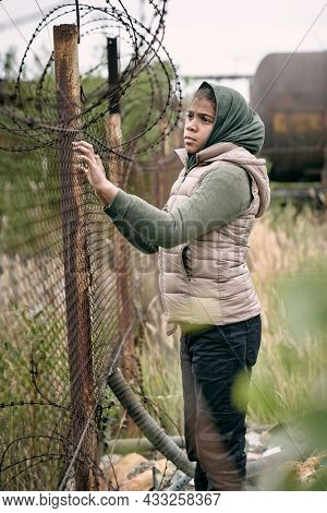 Sorrowful middle-eastern girl in headscarf and vest lost her parents during hostilities standing at barbed wire