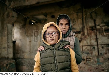 Portrait of two sisters in hoodies standing inside of abandoned house, they left alone after hostilities