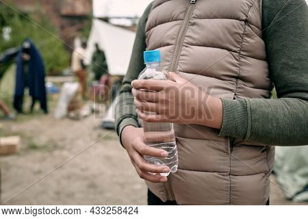 Close-up of unrecognizable black girl in warm vest standing with bottle of water against migrant camp