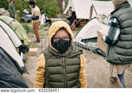 Portrait of mixed race child in hoodie, vest, eyeglasses and cloth mask standing in refugee camp