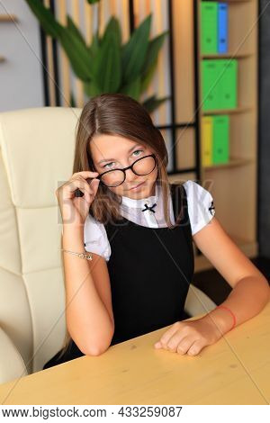 Young Beautiful Girl With Poor Eyesight Wearing Glasses. A Teenager In A School Office. Portrait Of