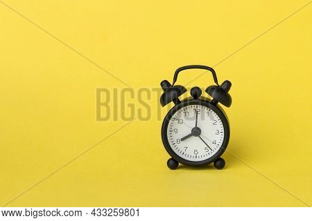 A Small Alarm Clock On Yellow Background, 8 O'clock