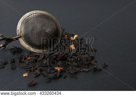 A Strainer For Tea And A Slide Of Dry Natural Tea For Making A Warming Drink On A Dark Background. P