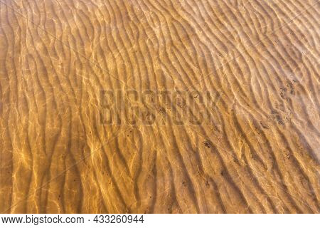 Yellow Sandy Seabed Is Under Shallow Water With Ripple Pattern, Natural Background Photo