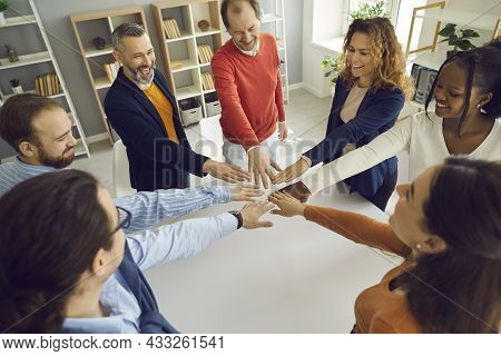 Happy Multi-ethnic People Group Join Helping Hands In Circle Together In Office