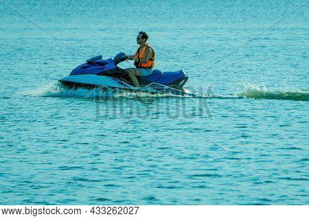 Chelyabinsk, Chelyabinsk Oblast, Russia - August 25.2021 A Man In A Life Jacket Rides A Jet Ski On T