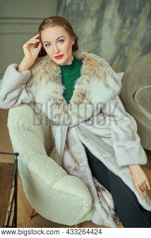 Fur coat fashion. Pretty young blonde woman in an expensive mink and lynx fur coat posing in a white armchair. Portrait in a classic luxury interior.