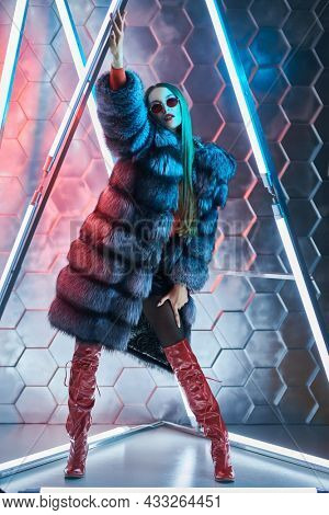 Full length portrait of a bright charismatic girl in expensive silver fox fur coat and leather boots posing among the neon lamps. Modern fur coat fashion. Techno style.