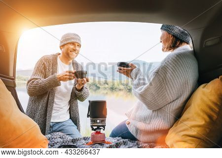 Car Trunk View Of Chatting Couple Dressed Warm Knitted Clothes Enjoying Gas Stove Prepared Coffee An