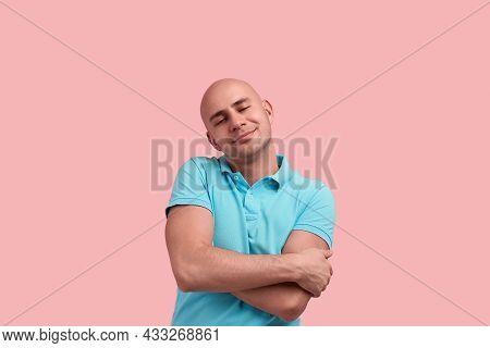 Love Myself. Glad Bald Homosexual Man With Bristle Hugs Himself, Keeps Eyes Closed, Smiles With Plea
