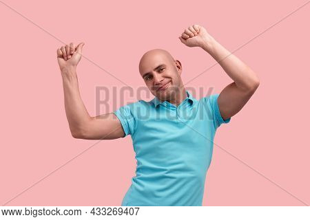 Optimistic Bald Homosexual Man With Bristle Raises Arms And Dances, Feels Relaxed, Happy With Upcomi