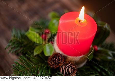 Burning Christmas red candle with decoration of fir, holly and little pine cones. Close up of advent candle with fir leaves and holiday decoration. Top view of xmas candle burning with decoration.