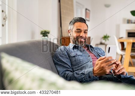 Happy mid adult man using smartphone device while sitting on sofa at home. Smiling mature indian man lying on couch reading messages on mobile phone while listening to music with wireless earbuds.