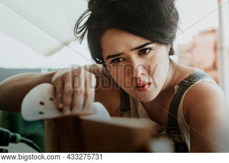 Determined female carpenter preparing wood with sandpaper