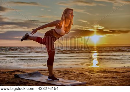 Woman Is Training Yoga On Seaside During Sunset.