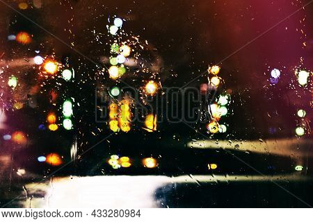 Abstraction Of The Night City, Color Indistinct Fires In Rays Of Light. Reflection About Damp Asphal