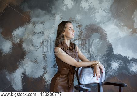 Portrait Of A Beautiful Young Business Woman With Brown Hair In A Brown Dress. Side View Of Happy Sm