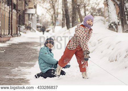 26th Of March 2021, Russia, Tomsk: Kids Throwing Snowballs At The Street In Winter