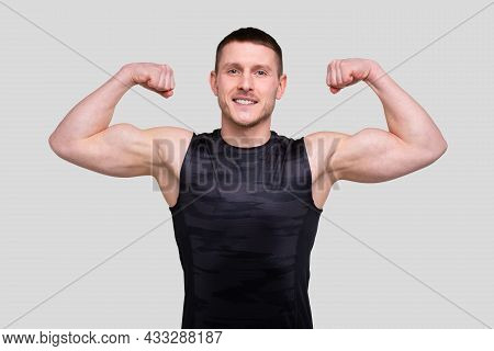 Man Showing Biceps Hands Up. Sportsman Showing Muscles. Abs, Biceps Muscles