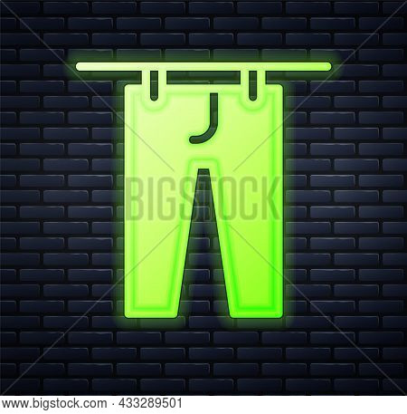 Glowing Neon Drying Clothes Icon Isolated On Brick Wall Background. Clean Pants. Wash Clothes On A R