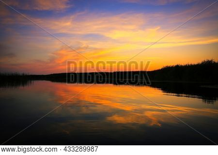 evening landscape with evening sky over lake water surface