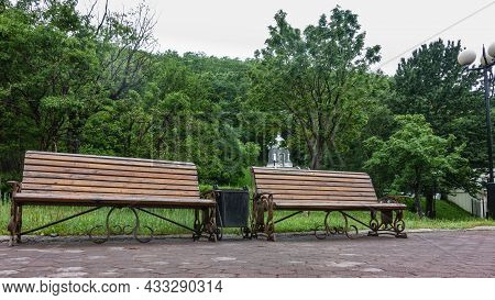 There Are Wooden Benches On The Paved Path In The Park. Behind - A Lawn, Green Trees. An Old White C