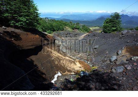 Dark ash and frozen lava ravine on side of Villarrica volcano along Villarrica Traverse hiking trail in Villarrica national park, Nature of Chile