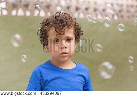 Beautiful 4-5 Year Old Caucasian Boy With Curly Hair And Freckles Looking Into The Camera Surrounded