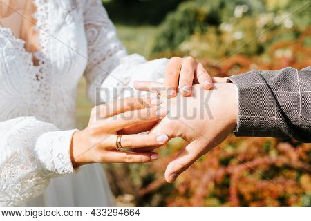 Close-up Of An Outdoor Wedding Ceremony, Bride Puts Ring On Groom's Hand, Newlyweds Exchange Rings.