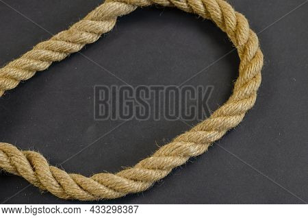 Hemp Rope On A Black Background. Twisted Rope Is Made Of Natural Materials. Nautical Theme.
