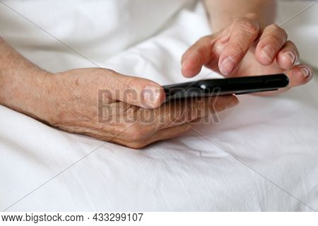 Elderly Woman With Smartphone In A Bed, Mobile Phone In Wrinkled Female Hands Close Up. Concept Of O