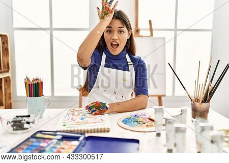 Young brunette woman at art studio with painted hands surprised with hand on head for mistake, remember error. forgot, bad memory concept.