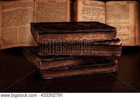Stack Of Old Worn Shabby Jewish Book In Leather Binding And Open Blurred Torah In The Background In